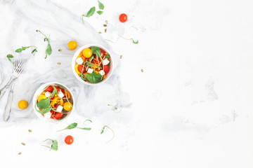 Spring salad with arugula, feta cheese, bell pepper and cherry tomatoes. Flat lay, top view