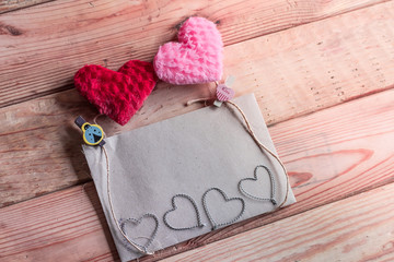 Paper for your text and small red hearts on old wood background.