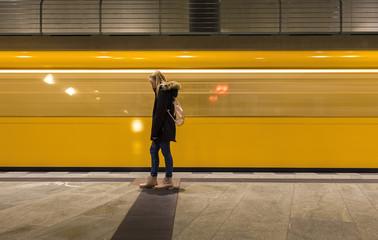 junges Mädchen vor abfahrendem Zug der U-Bahn in Berlin