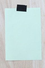 Green notepad paper of empty and copy space on wooden background