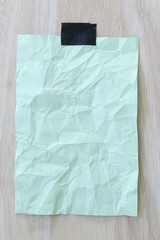 Green notepad paper wrinkled of empty and copy space on wooden b
