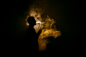 The man smoke an electronic cigarette against the background of the flame
