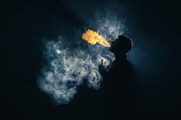 The man smoke an electronic cigarette against the background of bright light