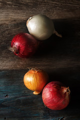 Onions of different varieties and colors. Dark gray background.