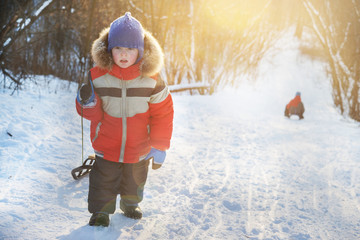 Children sledding in the winter.little boy carries a sled on the hill in winter