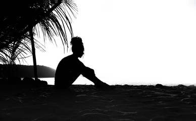 woman sit alone on the sand beach,back lit silhouette