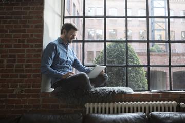 Mature man sitting on window sill, using laptop