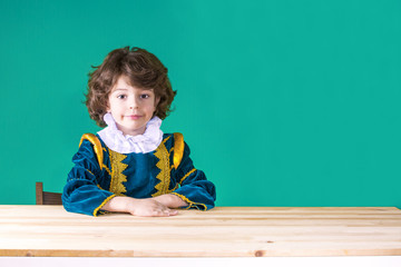Cute curly-haired boy in the clothes of Prince put his hand on the table looking at the camera. Close-up. Turquoise background.