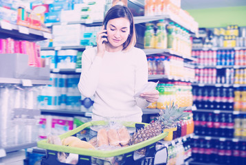 Laughing female talking on phone about shopping