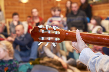 People listening a female guitarist singing song