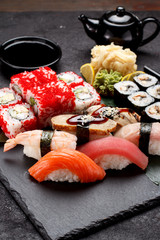 Japanese cuisine. Sushi set on a stone plate and concrete background.