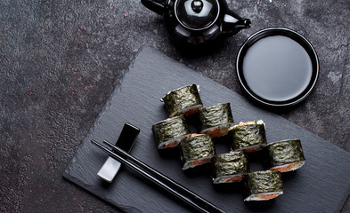 Japanese cuisine. Sushi roll on a stone plate and dark concrete background. Top view.