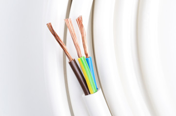 Electrical cable with three insulated conductors. Power cable cross-section. Cable jacket with wire insulation and flexible stranded copper wires. IEC standard color code. Macro photo from avove.