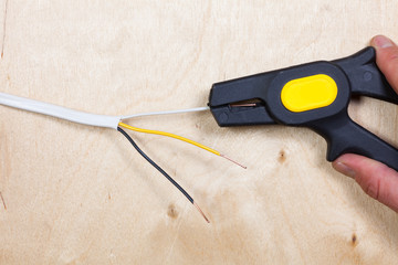 Person uses an automatic wire stripper to strip the electrical insulation from electric wires