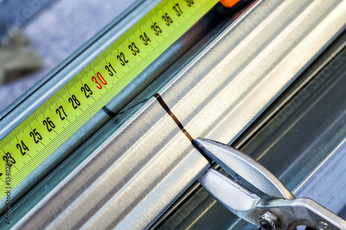 Person cuts a metal stud with snip cutter while constructing ...