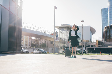 young contemporary businesswoman walking holding luggage