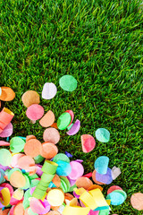 Buntes Konfetti und Luftschlangen auf Gras als Hintergrund
