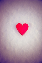 romantic background red heart lies on the snow