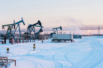 Oil Field. Winter industrial landscape with an oil pump and torch in the background.