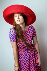 Fashion Brunette Lady in red hat and red blue dress on white grey background. studio