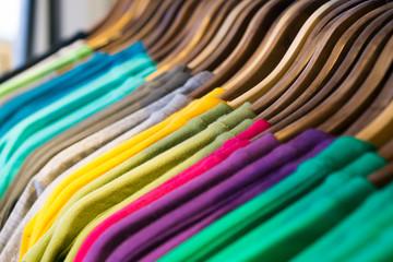 Textildruck / Bunte T-Shirts auf Kleiderbügeln sortiert