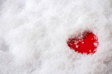 Single red heart in the snow, top view