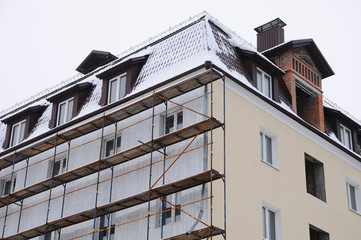 Renovation of house with scaffolding. Reconstruction of old building