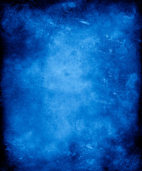 Blue grunge vintage textured background with faded central area for your text or picture.