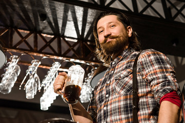 hipster bearded man in a plaid shirt is holding a glass of beer