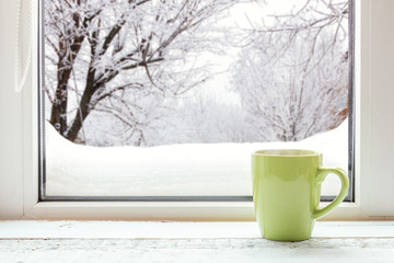 Cup of coffee on the window sill. In the background, a beautiful winter landscape in snow. Cozy home concept.