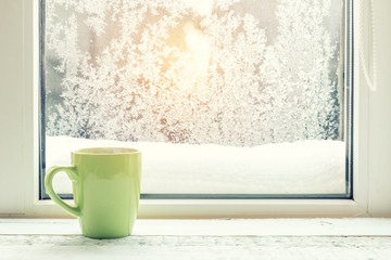 Cup of coffee on the window sill. In the background frosty pattern on window as a Christmas background Cozy home concept.