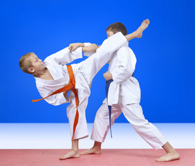 Two athletes in karategi beat kick arm and leg