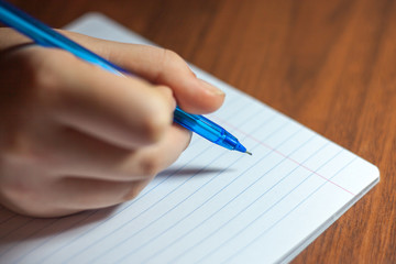 A close photo of a persons writing a letter with a pen