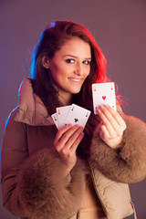 Beautiful brunette holding four aces as a sign for poker game, g