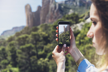 Hipster girl making photo on smartphone mobile closeup, view tourist using gadget phone in travel on background mountains and sky landscape; finger touch screen cellphone mockup nature