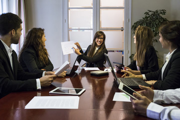 Cheerful woman showing documents to colleagues in boardroom