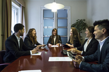 Cheerful lawyers discussing in boardroom