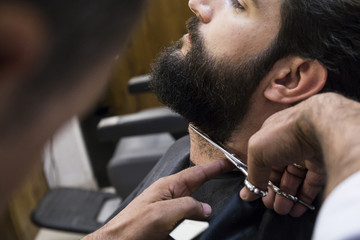 Cropped image of barber cutting man's beard in shop
