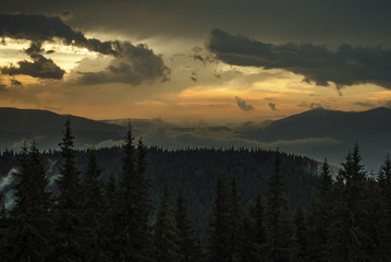 Scenic view of tree mountains against cloudy sky during sunset