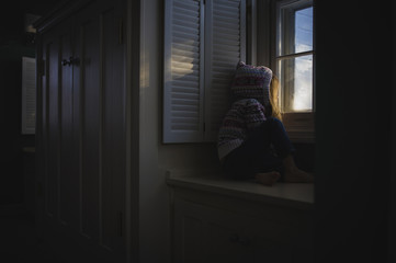 Girl in hooded shirt looking through window while sitting on cabinet at home