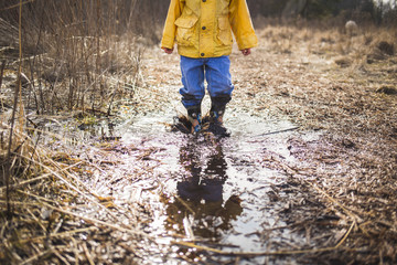 Low section of boy standing in dirty puddle