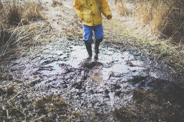 Low section of boy walking in dirty puddle