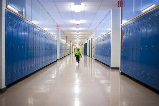Rear view of boy running in school corridor