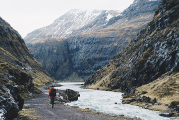 Rear view of man walking road by river against mountains