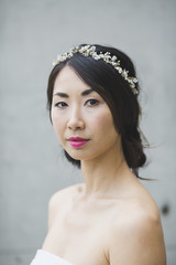 Portrait of woman wearing tiara while standing against white wall