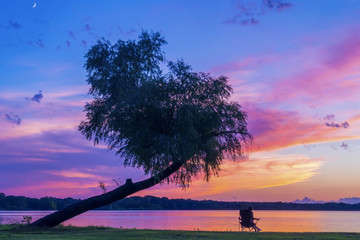 Woman relaxing at lakeshore against dramatic sky during sunset