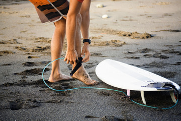 Low section of man tying surfboard while standing on wet sand at beach