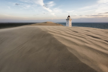 Lighthouse on sandy beach against sky during sunset