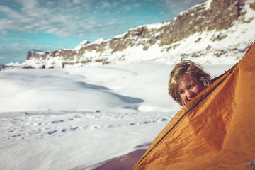 Portrait of happy woman peeking through tent at Grand Teton National Park during winter