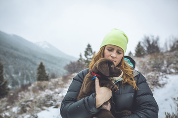 Woman with Chocolate Labrador standing against sky during winter